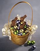 Easter Basket with Chocolate Bunnies and Foil Wrapped Eggs on Lavender Background