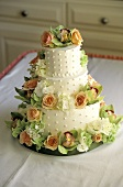 A 3-Tiered Wedding Cake Decorated with Roses and Hydrangeas