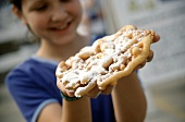 Funnel Cake with Powdered Sugar Held by Smiling Girl