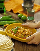 Woman's Hands Holding a Dish of Mexican Style Shrimp