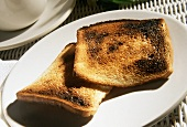 Two Slices of Burnt Toast on a White Plate