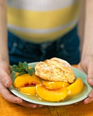 Person holding plate of peach cobbler
