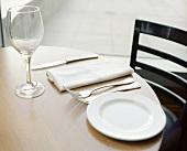 Einzelnes Gedeck mit weißem Teller, Besteck, Weinglas