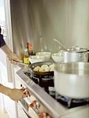 Person Adjusting Heat for Pan of Dumplings