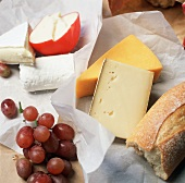 Various types of cheeses with grapes and bread