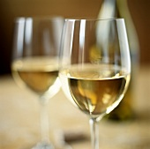 Two white wine glasses in front of bottle in background