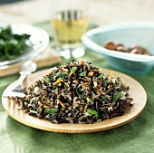 Wild rice salad with asparagus on wooden plate