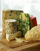 Various types of cheese on chopping board