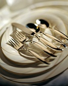 Silver cutlery on gold-rimmed plates
