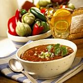 Gazpacho in soup bowl; ingredients; bread