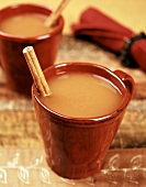 A mug of hot cider with cinnamon stick