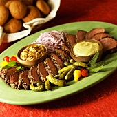 Sliced Beef Tenderloin on a Platter with Remoulade and Mustard Sauces