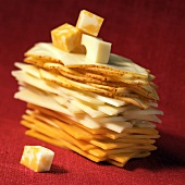 Slices of different types of cheese and diced cheese in pile