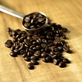 Roasted coffee beans on wooden background, coffee measure