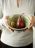 Woman holding bowl of pears in red wine