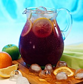 Fruit punch with ice cubes in glass jug