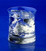 Glass or water or gin & tonic with ice against blue background