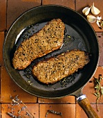Two Fried Steaks with Garlic in a Frying Pan