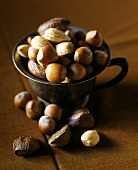 Various nuts in cup on brown background