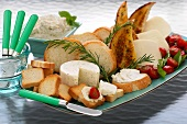Platter with slices of white bread, soft cheese, tomatoes etc.