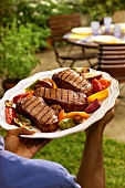 Man carrying platter of barbecued steaks to garden table