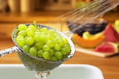 Green grapes being washed in a sieve