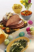 A Baked Ham for Easter with Asparagus and Colorful Easter Eggs