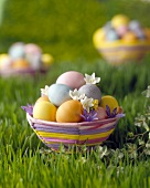 Coloured Easter baskets with eggs and flowers on grass