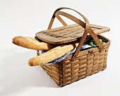 A Picnic Basket with Two Baguettes and Green Grapes