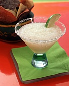 Frozen Margarita with lime in glass with salted rim