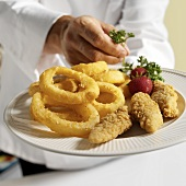 A Chef Placing a Parsley Garnish on a Plate of Chicken Tenders and Onion Rings