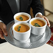 A Waiter Serving Three Bowls of Cream of Tomato Soup with Oregano
