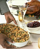 Hands putting a dish of bread stuffing on a table