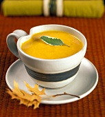 A Cup of Pumpkin Soup with a Sage Leaf