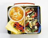 A Child's Lunchbox with Pasta Salad and Sliced Oranges