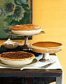A Pecan Pie, a Squash Pie and an Apple Pie on a Wooden Table with a Bowl of Cream
