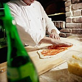 Chef Spreading Tomato Sauce on Pizza with Hands