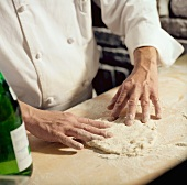 Chef Flattening Pizza Dough with His Hands
