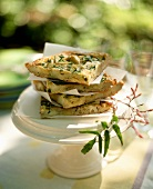 Slices of Artichoke Frittata on a Pedestal Dish Outside