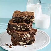 A Stack of Walnut Chocolate Brownies with a Glass and Bottle of Milk