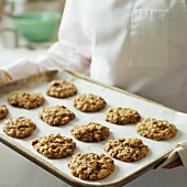 Chef serving oat biscuits on baking tray