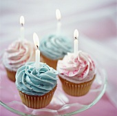 Pink and blue cup-cakes with burning candles