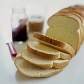 White bread, sliced; jam; peanut butter