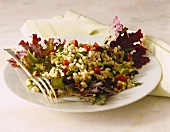 Salad leaves with pearl barley, peppers and spring onions