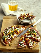 Pizza with tomatoes, peppers and basil on chopping board