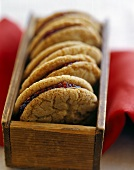 Biscuits filled with raspberry jam in wooden box
