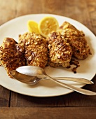 Chicken breasts with almond crust and lemons on plate