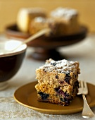 Piece of coffee cake with blueberries and icing sugar