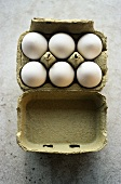 Six white eggs in egg box (overhead view)