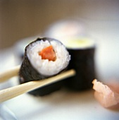 Chopsticks Holding a Maki Sushi